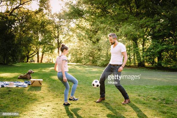 father and teenage daughter playing soccer in park