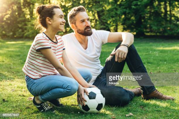 father and teenage daughter spending time together, sitting with soccer ball in park