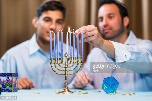 Father and teenage son lighting menorah