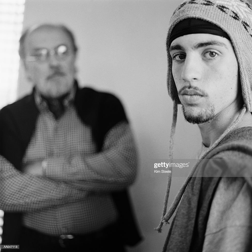Father and teenage son (16-18), portrait (focus on son, B&W) : Stock Photo