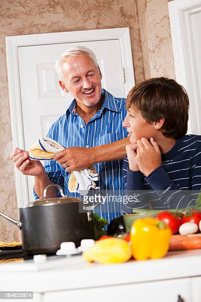 Father and teenage son talking in kitchen