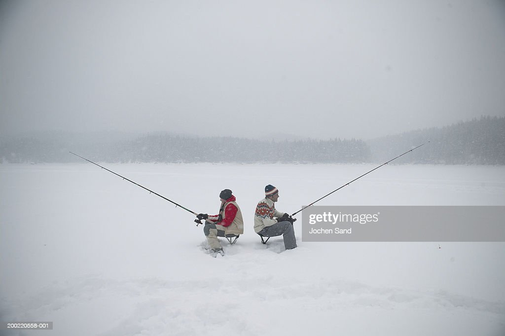 Father and teenage son with fishing rods on frozen lake for Frozen fishing pole