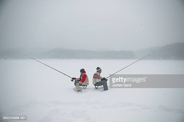 Father and teenage son (13-15) with fishing rods on frozen lake, side view