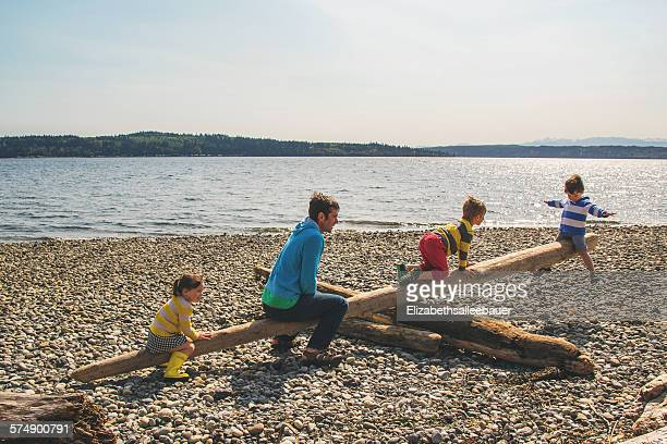 Father and three children playing on beach with makeshift seesaw