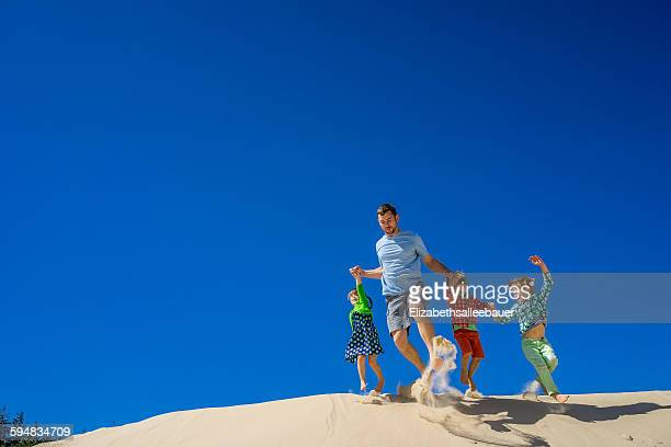 Father and three children running down a sand dune
