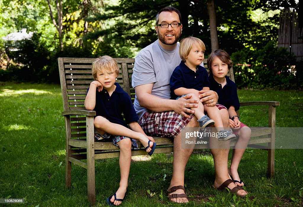 Father and three sons, portrait on bench : Stock Photo