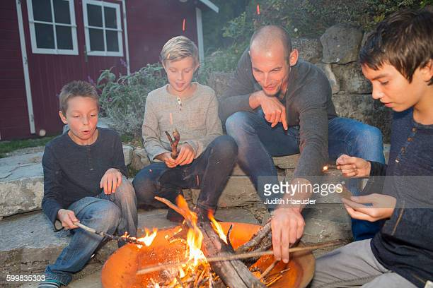Father and three sons sitting by garden campfire at dusk