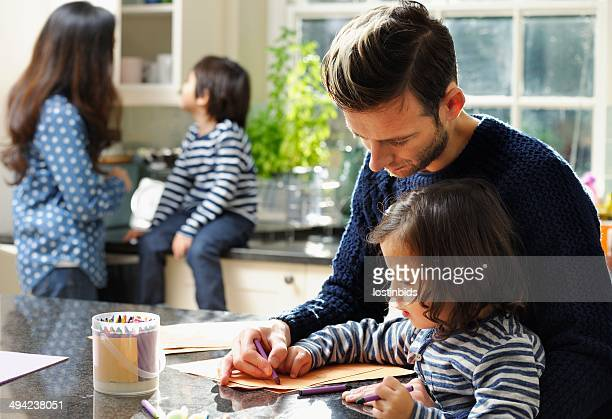 Father And Toddler Doing Artwork In The Kitchen