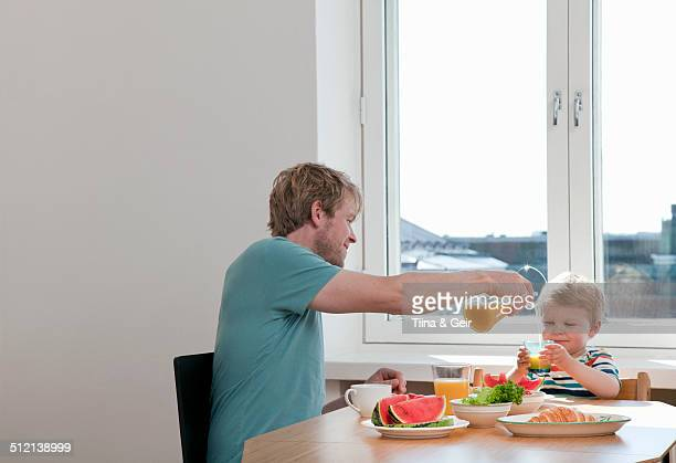 Father and toddler son having breakfast at kitchen table
