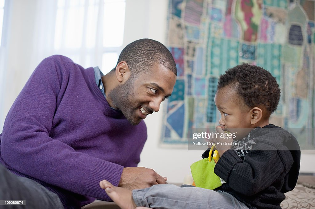 Father and toddler son lookng at each other : Stock Photo