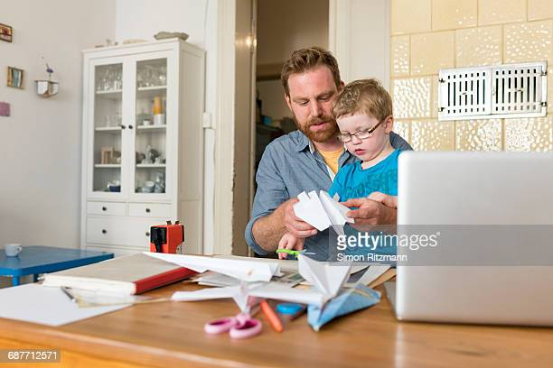 Father and toddler son making paper plane at home