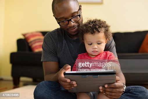 Father and toddler using digital tablet