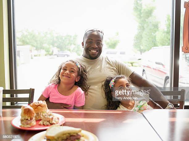 Father and twin daughters in restaurant