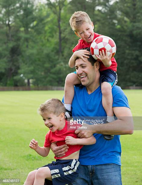 Father and twin  sons playing on soccer field