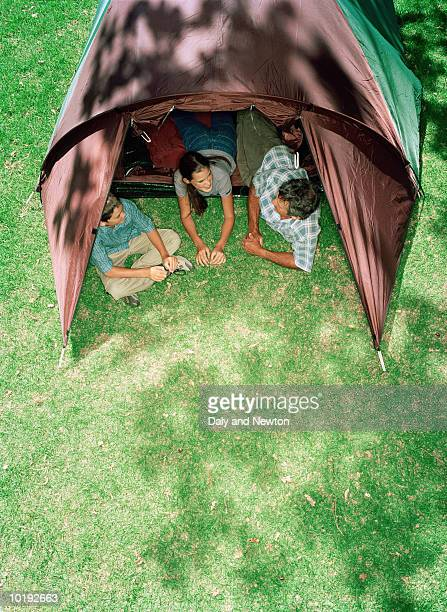 Father and two children (12-14) in tent, elevated view