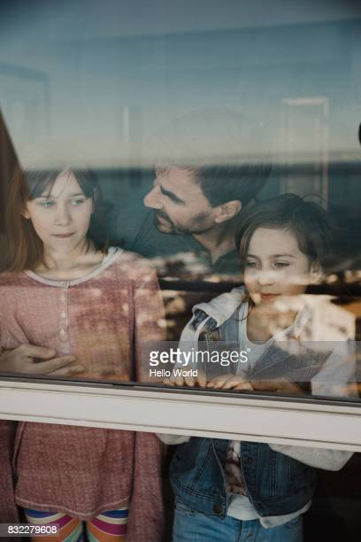 Father and two daughters behind a window