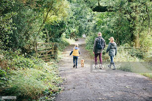 Father and two girls walking dog on rural road