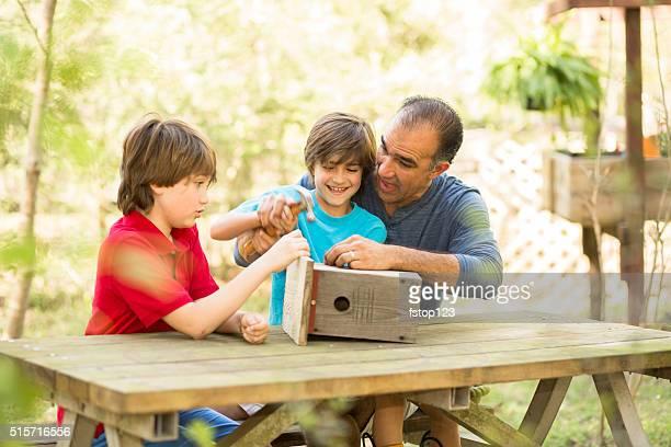 Vater und zwei Söhne Gebäude Vogelhäuschen im Freien. Zeit für die Familie!