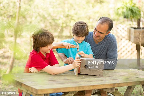 Father and two sons building birdhouse outdoors. Family time!