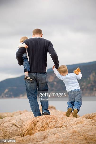 父と息子の近くの 2 つの岩のクライミング海