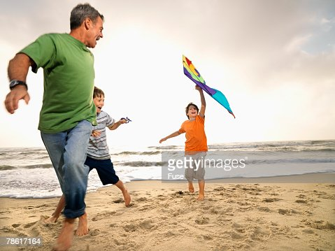 Father and Two Sons on Beach Flying Kite : Stock Photo