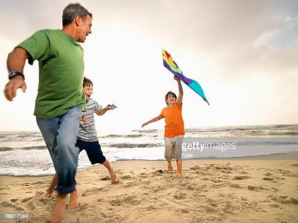 Father and Two Sons on Beach Flying Kite