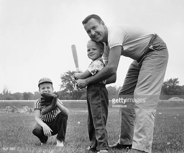 Père et ses deux enfants jouant au baseball