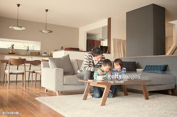 Father and two sons playing with a digital tablet together