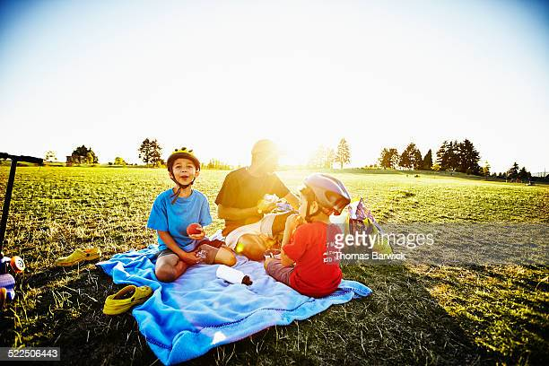 Father and two young sons having picnic in park
