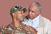 Father and US Marine Corps soldier looking at each other over brown background