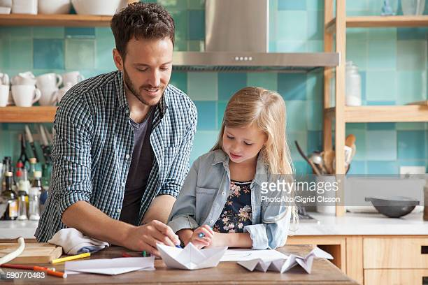 Father and young daughter drawing in kitchen