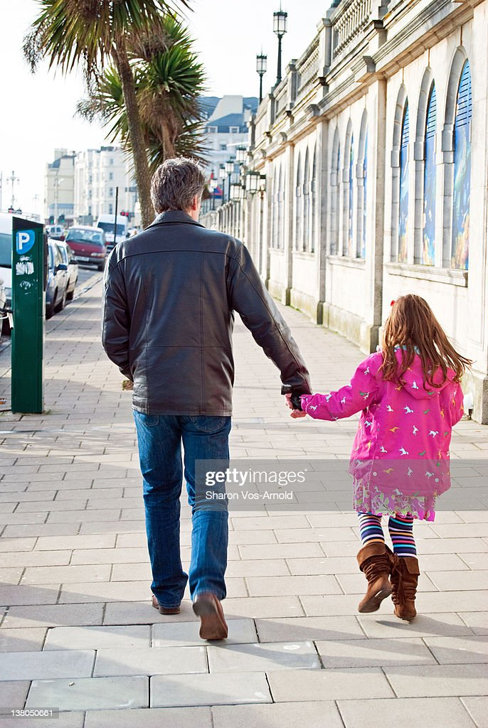 Father and young daughter holding hands walking : Stock Photo
