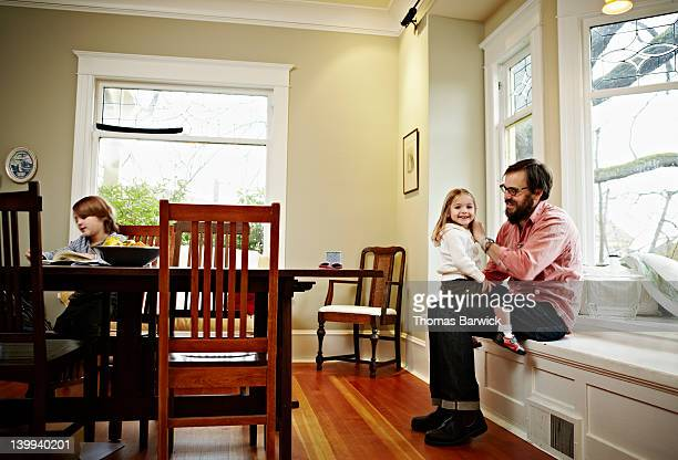 Father and young daughter sitting near window