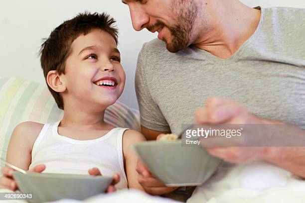 Father and young son having breakfast in bed