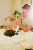 Father and young son play fighting on bed