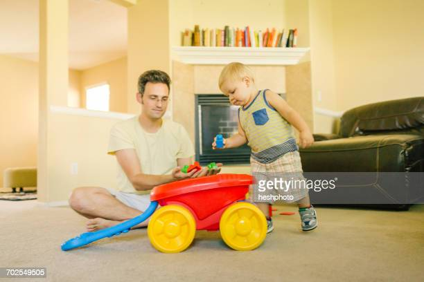 Father and young son playing together at home