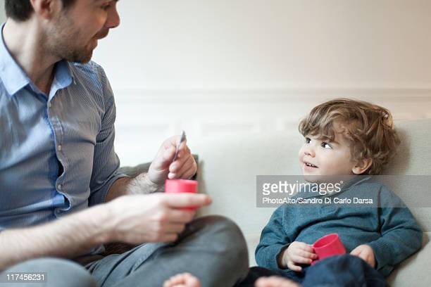 Father and young son playing with toy tea set