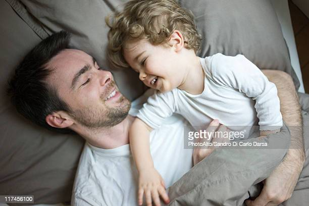 Father and young son relaxing together in bed, portrait