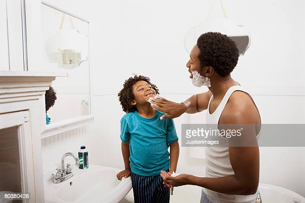 Father applying lather to boy's face