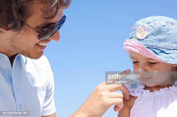 Father applying sunscreen to daughter's (12-18 months) face