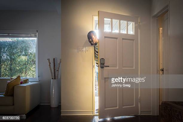 Father arriving home peeping through open front door