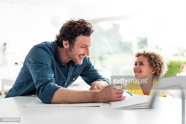 Father assisting daughter in doing homework