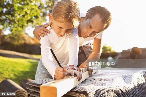 Father assisting daughter in measuring plank