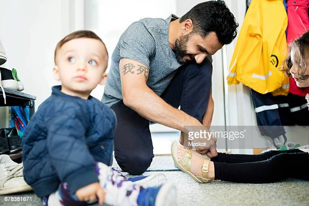 Father assisting daughter to put on sandal while toddler sitting in foreground