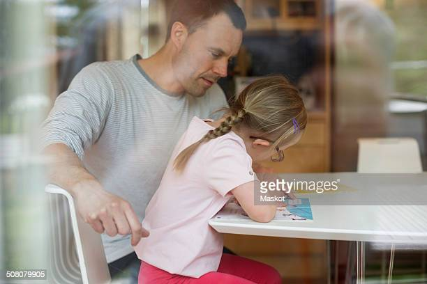 Father assisting handicapped girl in studies at table