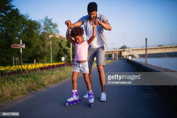 Vater seiner Tochter beim Rollschuhlaufen bei Sonnenuntergang zu unterstützen.