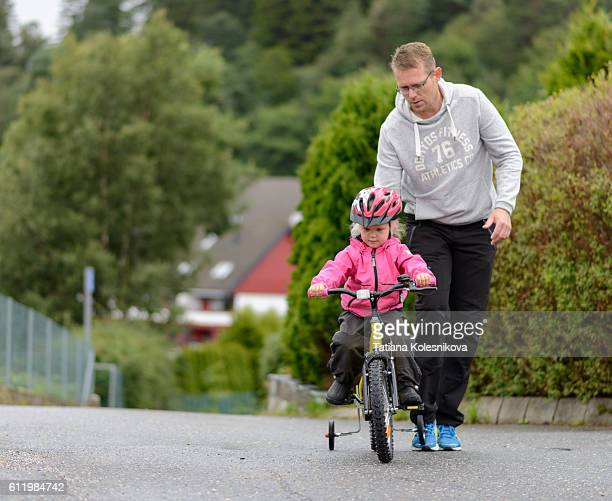 Father assisting his little daughter in riding a bike