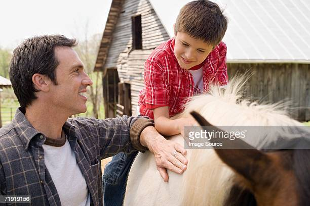 Father assisting son horseback riding