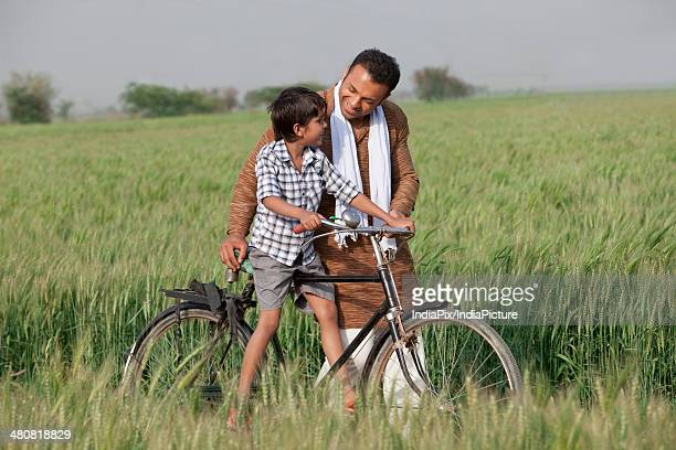 Father assisting son in riding cycle at farm