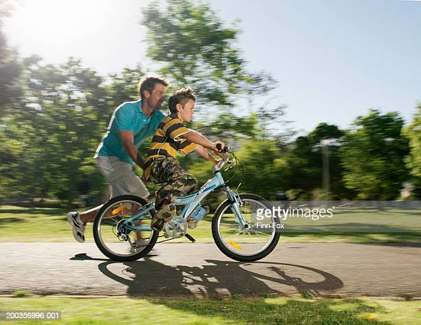 Father assisting son (9-11) on bicycle along pathway, side view